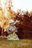 Frau, die ein Buch im Park liest Lizenzfreie Stockbilder
