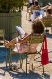 Frau, die ein Buch im Park liest Lizenzfreie Stockfotos