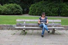 Frau, die ein Buch im Park liest Stockfotografie