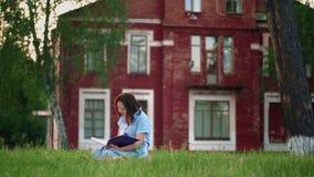 Frau, die ein Buch im Park liest stock footage