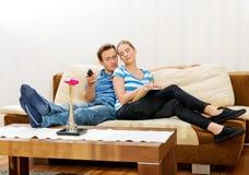 Frau, die ein Buch liest, während ihr Ehemann im Wohnzimmer fernsieht Stockbild
