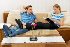 Frau, die ein Buch liest, während ihr Ehemann im Wohnzimmer fernsieht Lizenzfreie Stockbilder