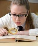 Frau, die ein Buch mit einem Vergrößerungsglas liest Lizenzfreie Stockfotografie