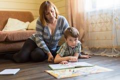 Frau, die ein Buch mit ihrem kleinen Sohn sitzt auf dem Boden im Haus liest Stockbilder