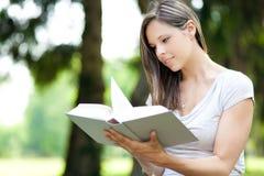 Frau, die ein Buch am Park liest Stockbilder
