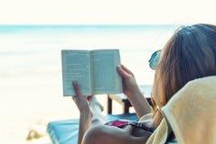 Frau, die ein Buch am Strand liest Stockfotos