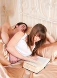 Frau, die ein Buch- und Mannschlafen liest Stockbild