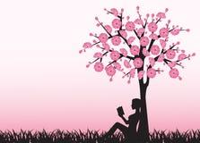 Frau, die ein Buch unter einem Baum liest Lizenzfreies Stockbild