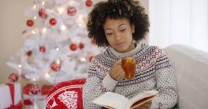 Frau, die ein Buch vor einem Weihnachtsbaum liest Stockbild