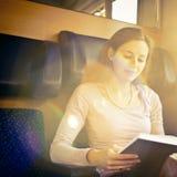 Frau, die ein Buch während auf einer Serie liest Stockfoto