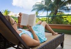 Frau, die ein Buch während tropischen Ferien sich entspannt und liest Stockfotos