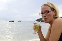 Frau, die ein Cocktail genießt Lizenzfreie Stockfotografie