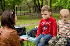 Frau, die ein ernstes Gespräch mit einem kleinen Jungen hat Stockbilder