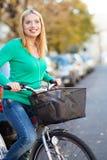 Frau, die ein Fahrrad in der Stadt reitet lizenzfreies stockbild