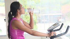 Frau, die ein Fahrrad und ein Trinkwasser reitet stock video footage