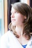 Frau, die ein Fenster bereitsteht stockfotos