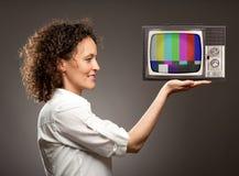 Frau, die ein Fernsehen hält lizenzfreie stockfotos