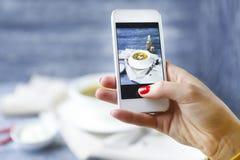 Frau, die ein Foto der Fischsuppe mit Smartphone macht Lizenzfreies Stockfoto