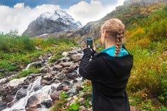 Frau, die ein Foto des Berges auf Smartphone macht Lizenzfreies Stockfoto