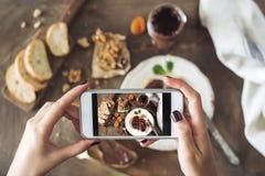 Frau, die ein Foto des Frühstückstisches macht lizenzfreie stockfotografie