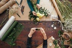 Frau, die ein Foto eines Blumenstraußes macht Stockbild