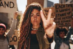 Frau, die ein Friedenszeichen während des Protestes zeigt lizenzfreies stockbild