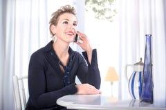 Frau, die ein frohes Handygespräch hat Stockfoto