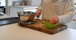 Frau, die ein Gemüse mit Messer auf Küche worktop hackt stock video footage