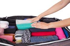 Frau, die ein Gepäck für Reise verpackt Stockfotos