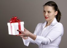Frau, die ein Geschenk anbietet Lizenzfreie Stockfotos