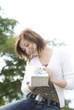 Frau, die ein Geschenk anhält Lizenzfreies Stockfoto