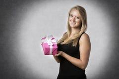 Frau, die ein Geschenk anhält Lizenzfreie Stockfotos
