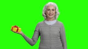 Frau, die ein Geschenk auf Farbenreinheitsschlüsselhintergrund hält stock footage