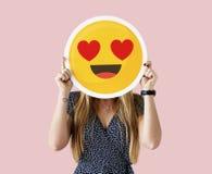 Frau, die ein Gesicht emoji hält stockbilder