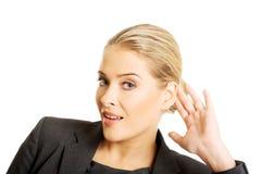 Frau, die ein Gespräch zufällig hört Lizenzfreie Stockfotografie