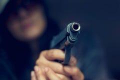 Frau, die ein Gewehr auf das Ziel auf dunklem Hintergrund zeigt lizenzfreies stockfoto