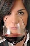 Frau, die ein Glas Rotwein riecht Stockfotografie