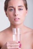 Frau, die ein Glas Wasser anhält Lizenzfreie Stockbilder