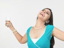 Frau, die ein Glas Wasser trinkt Stockfotografie