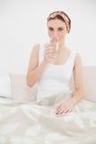 Frau, die ein Glas Wasser untersuchend die Kamera trinkt Lizenzfreies Stockbild