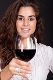 Frau, die ein Glas Wein und Lächeln anhält stockfoto