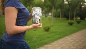 Frau, die ein Glasgefäß mit den Dollar laufen hinunter eine Stadtstraße hält Konzept-Finanzierung, Rabatte, Verkauf stock video