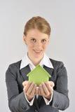 Frau, die ein grünes Haus darstellt Lizenzfreie Stockfotos