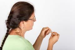 Frau, die ein Hörgerät hält Stockbilder