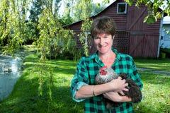 Frau, die ein Huhn außerhalb der Scheune hält lizenzfreie stockfotos