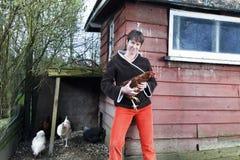 Frau, die ein Huhn hält stockbild