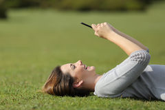 Frau, die ein intelligentes Telefon stillsteht auf dem Gras in einem Park verwendet Lizenzfreie Stockfotos