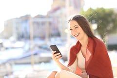 Frau, die ein intelligentes Telefon verwendet und Kamera betrachtet Lizenzfreie Stockfotos