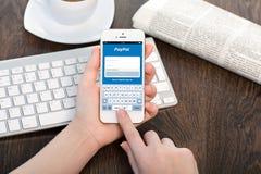 Frau, die ein iPhone mit Ausrichtung Paypal hält Lizenzfreies Stockbild