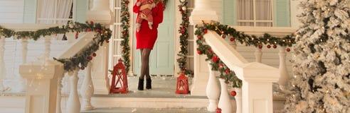 Frau, die ein Kind auf der Veranda des Hauses, nahe bei den Weihnachtslichtern hält lizenzfreies stockbild